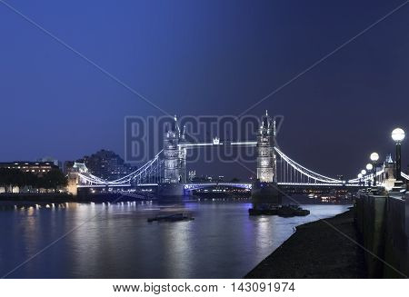 Tower Bridge London England transition from twilight to darkness with water reflections