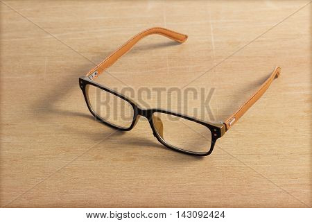 The Brown glasses on wood table .