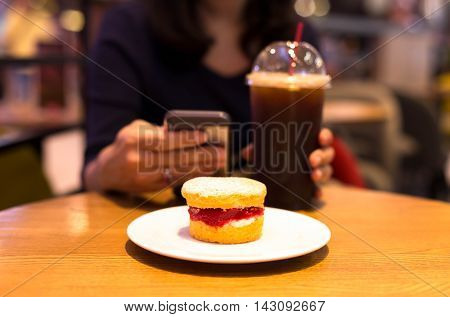 Focus on strawberry jam scone and woman use cellphone with iced coffee blur background