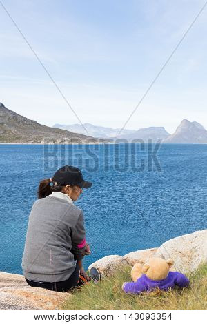 Single woman sitting at the stone beside green grass with her teddy bear looking at the sea - Concept for single and travel
