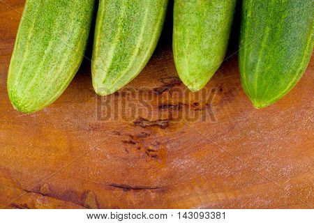 fresh green cucumbers on wooden background healthy raw vegetable food isolated
