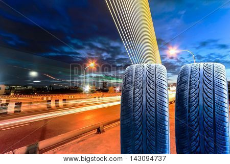 New tire and bridge at night with light trails