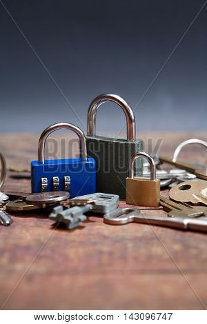 Three padlocks near keys on wooden board against dark background
