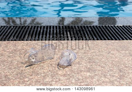 Pair of baby flipflops sitting on a side of swimming pool floor