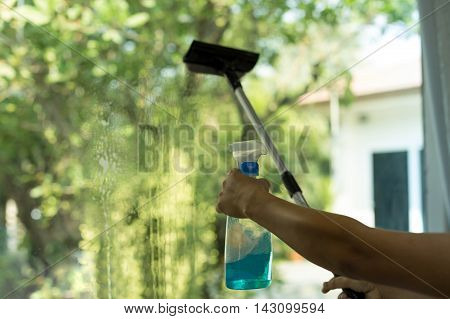 Selected focus Hand spraying window with special cleaner on a window