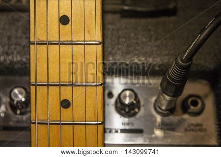 Guitar neck over amplifier device and audio cord with jack closeup