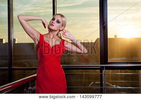 Young beautiful glamorous blonde girl in a red dress posing on the background of glass showcase. She looks away.