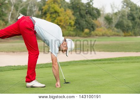 Golfer Taking The Ball From Hole