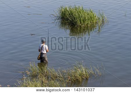 Fisherman catches a fish in the Volga peals. Catching carp and bass in the stream. Healthy lifestyle.