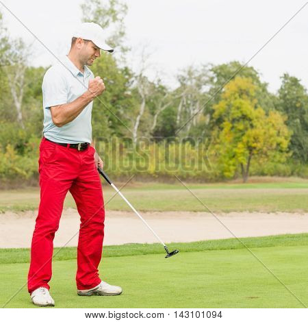 Satisfied golfer after successful putt, toned image, vertical image