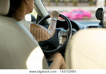 Woman with cell phone on her lap while driving