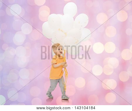 childhood, birthday, holidays and people concept - happy little baby boy with bunch of balloons over rose quartz and serenity lights background