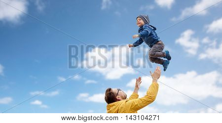 family, childhood, fatherhood, leisure and people concept - happy father and little son playing and having fun outdoors over blue sky and clouds background