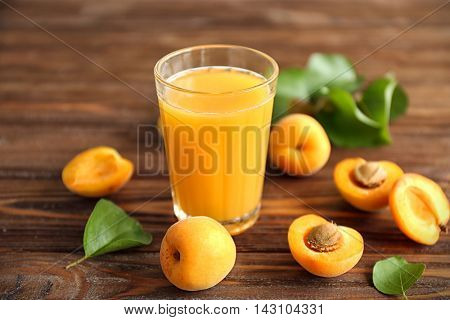 Juice and few apricots on wooden table