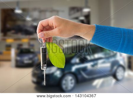 environment, people, transport and ecology concept - close up of hand holding key with green leaf trinket over car show or shop background