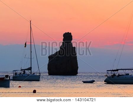 Sunset at Benirras Beach, a famous place on Ibiza Island. Anchored boats and rock in the water.