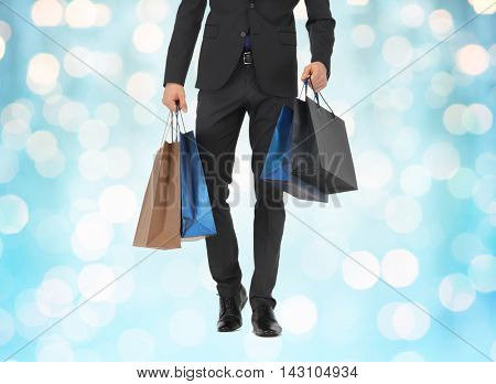 people, sale, fashion and consumerism concept - close up of man in suit with shopping bags over blue holidays lights background