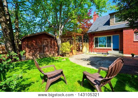 Backyard View With Concrete Patio And Small Shed.