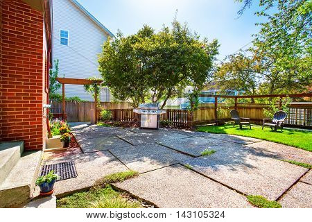 Backyard View With Concrete Patio And Barbecue.