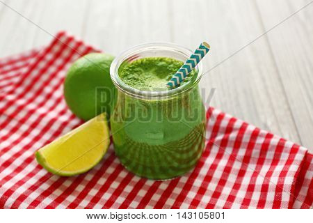 Tasty smoothie drink with lime on table