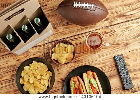 Glass of beer with bottles, snack and ball on wooden background