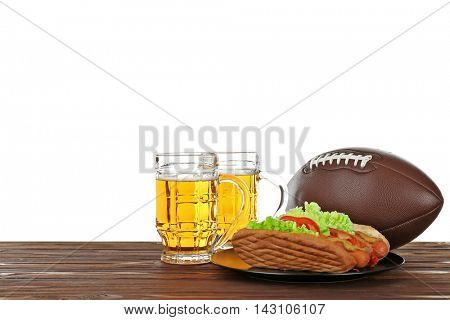 Two glass of beer, ball and snack on wooden table with white background