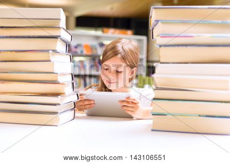 Little Girl Looks At Her Touch Pad Tablet Device Surrounded With Piles Of Books In Library