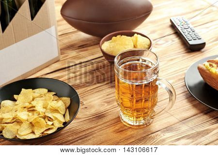 Glass of beer with snack and ball on wooden background