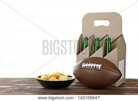 Six pack of beer, ball and snack on wooden table with white background