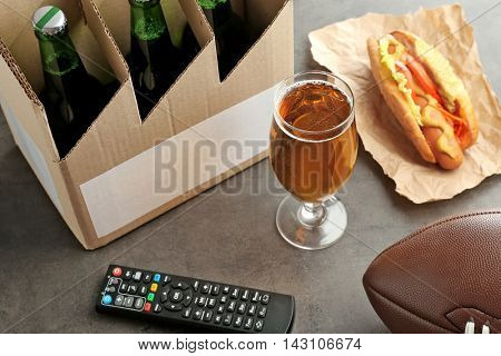 Glass of beer, bottles, snack and TV remote control on gray background