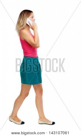 side view of a woman walking with a mobile phone. beautiful girl in motion.  backside view of person.  Rear view people collection. Isolated over white background. Blonde in a red sweater and green
