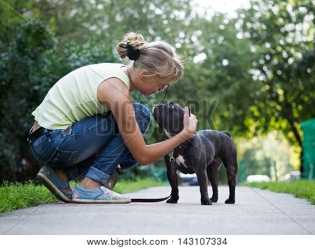 She stroked the dog while walking. Street of the city summer. French Bulldog in black with a collar and leash