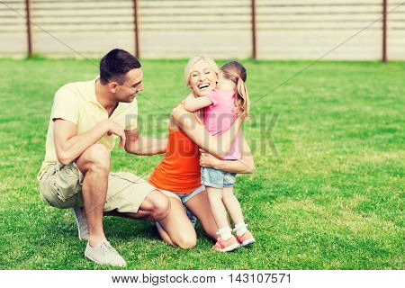 family, happiness, adoption and people concept - happy family hugging outdoors