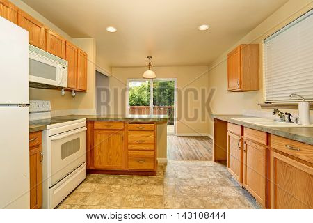 Classic American Kitchen Room With Wooden Cabinets And Tile Floor.