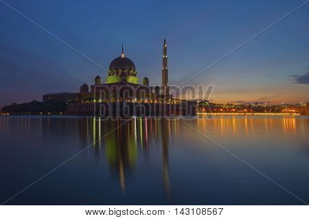 The view of one of the grand mosques in Putrajaya Putra Mosque during early morning with its reflection on the lake.