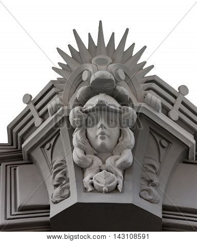 Carved facade element with a face and rays on an old building in Riga