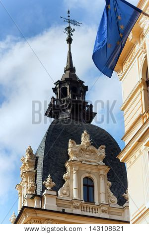 The spire of a weather vane on a historic Art Nouveau building with stucco decorations and the EU flag in Riga