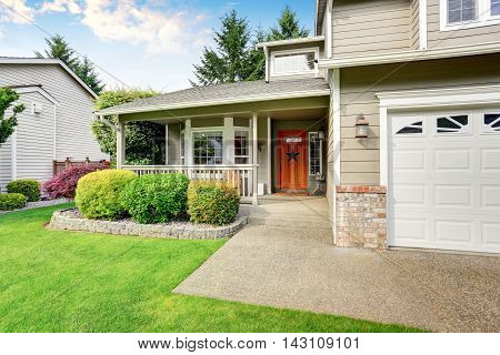American House Exterior With Double Garage And Well Kept Lawn.