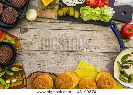 Flat background frame with tasty street food grilled beef burger in crispy shortbread with lettuce and mayonnaise served on cutting board a rustic wooden table with copyspace.