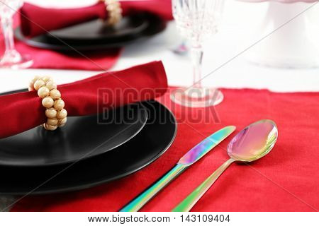 Beautiful table setting on red napkin