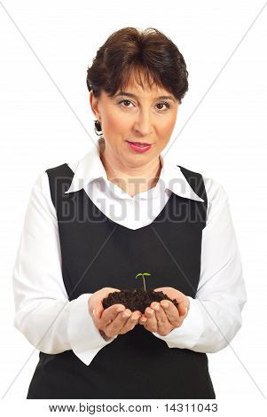 Corporate Woman Holding  Small Plant In Dirt