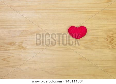 Red wool heart shape on wooden background with copy space