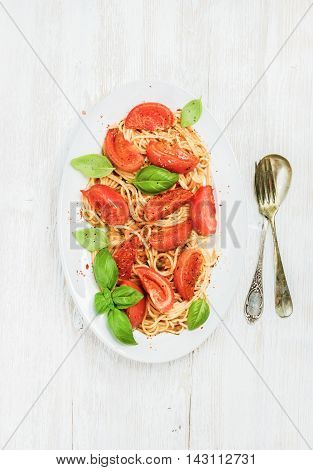 Pasta dinner. Spaghetti with roasted tomatoes and fresh basil in oval dish served with silver cutlery over white wooden background, top view, vertical composition