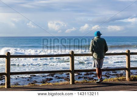 Man unidentified surfer standing looking out over ocean waves.
