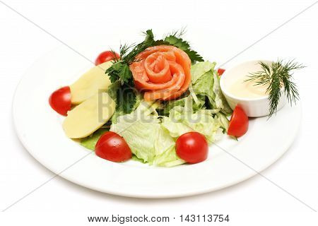 Salad with fish potatoes and tomatoes on white plate