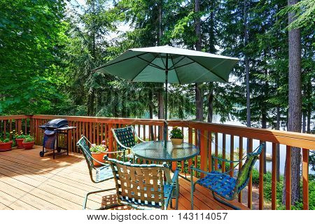 Balcony House Exterior With Patio Area And Opened Green Umbrella.