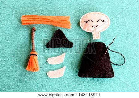 Fun Halloween sewing project for kids. Join the pieces of felt witch using a simple running stitch. Make a broom out of felt and wood branch. Sew Halloween witch doll. Step. Closeup. Top view