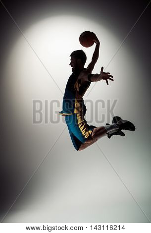 The silhouette view of a basketball player with a ball against gray studio background
