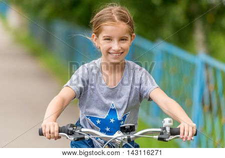 joyful smiling schoolgirl riding bicycle outside in a park