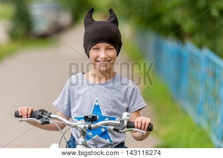 smiling schoolgirl in black hat with little horns riding bicycle outside